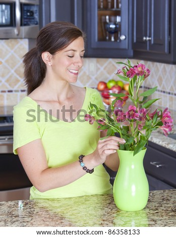 Pretty woman arranging a bunch of flowers in a vase