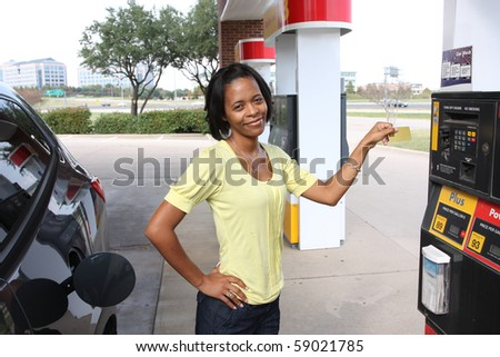 Pretty woman at gas station using credit card paying for gas