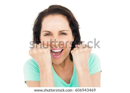 Pretty woman celebrating victory against white background #606943469