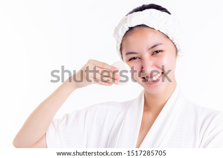 Pretty woman cleaning beautiful face by wiping, using cotton pads, cleansing lotion, facial toner. Attractive beautiful young lady has nice facial skin, bright facial skin. Facial skin care concept.