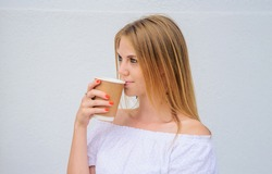 Pretty woman drinking coffee takeaway. Girl drinks Espresso, latte, cappuccino in paper cup.
