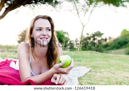 Pretty woman eating and holding half eaten green apple outdoors, lying on the grass in a park during sunset