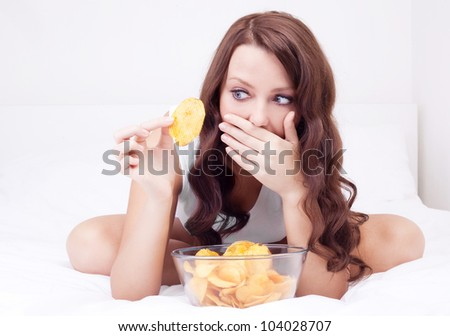 pretty woman eating potato chips in bed at home  and scared of gaining weight