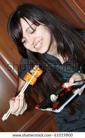 pretty woman eating sushi with chopsticks in dining room