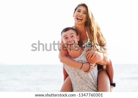 Pretty woman enjoying piggy ride on her boyfriends back,Pretty woman enjoying piggy ride on her boyfriends back #1347760301