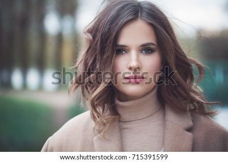 Pretty Woman Fashion Model with Blowing Curly Hair. Cute Girl Outdoors