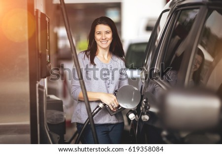 Pretty woman filling her car with petrol at gas station