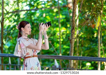 Pretty woman focusing her digital camera to take a photo in a colorful garden with forest foliage