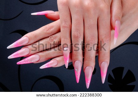 Pretty woman hand with perfect extreme long painted pink nails