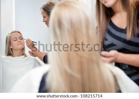 Pretty woman having eye shadow applied by a female makeup artist