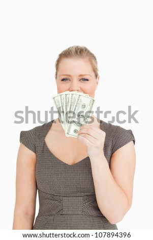 Pretty woman hiding her mouse with dollars banknotes against a white background