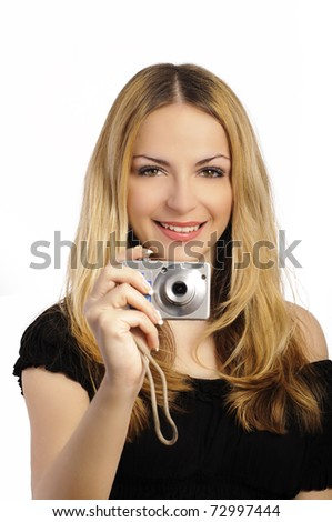 Pretty woman holding a digital camera and smiling, taking a photo, over white