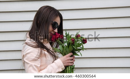 Pretty woman holding a gift in their hands. Pink tulips and flowers in their hands. #460300564