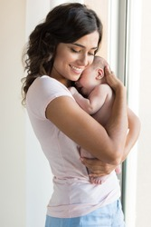 Pretty woman holding a newborn baby in her arms
