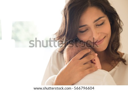 Pretty woman holding a newborn baby in her arms Stock photo ©
