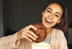 pretty woman holding big chocolate cookie and large cup tea with a happy face, laughing and smiling to camera. food, sweets and bakery concept
