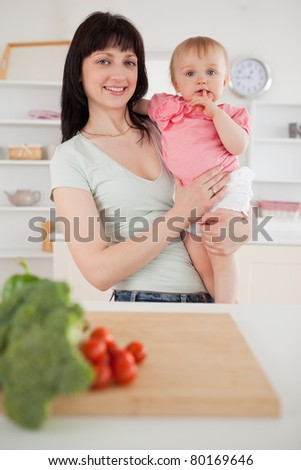 Pretty woman holding her baby in her arms while standing in the kitchen