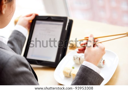 Pretty woman holding sushi with chopsticks and reading news using her tablet computer and free wifi at cafe on business lunch offer
