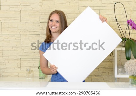Pretty woman holding up a blank white sign in front of her chest as she gives the camera a lovely smile - copyspace for your text or advertising
