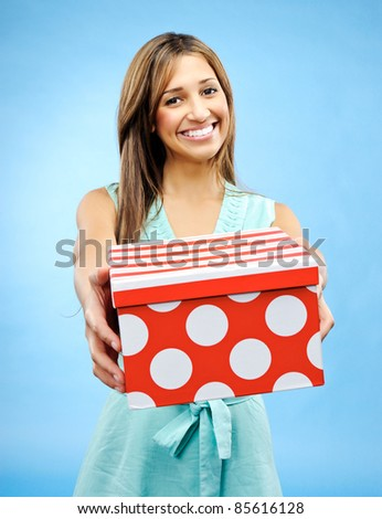 Pretty woman holds out a box to give a present for Valentine's Day