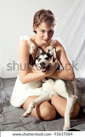 Pretty woman hugging her pet husky dog - stock photo