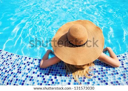 Pretty woman in a hat enjoying a swimming pool stock photo