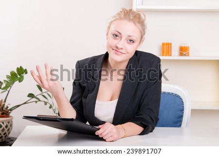 Pretty woman in a jacket gesturing at his desk at work - studio shoot