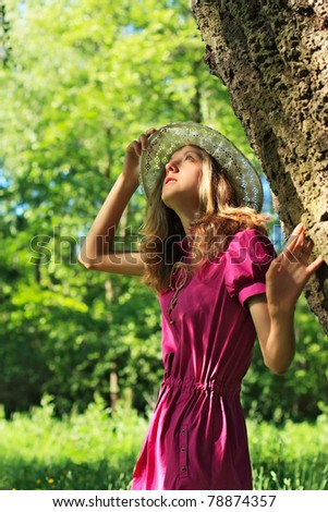 Pretty woman in a pink dress and white hat in the park