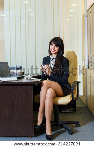 febc2a10ae4 Pretty woman in a short skirt drinking coffee in the office  314227091 · Young  sexy woman in black stockings sitting on workplace ...