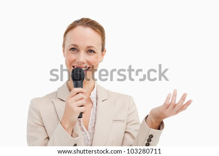 Pretty woman in a suit speaking with a microphone against white background