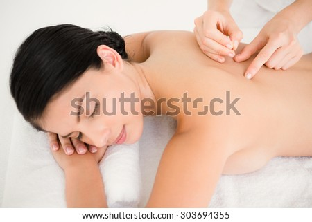 Pretty woman in an acupuncture therapy at the health spa