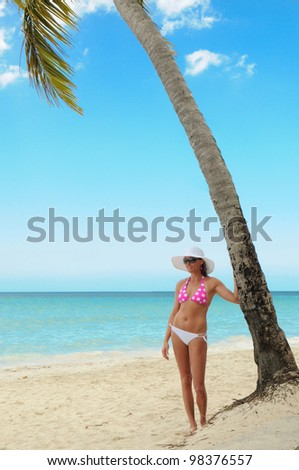 Pretty woman in bikini standing beside a Palm Tree on the white sand beach of a paradise island - stock photo