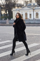 Pretty woman in black fur coat crossing street by crossroad. Full length fashion portrait