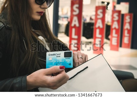Pretty woman in dark glasses sitting in mall department and holding credit card and white paper shopping bag at red discount signs background. Girl shows face side of bank card. Buying stuff on sale