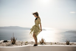 Pretty woman in floral outfit and hat moves on sea background. Happy girl in stylish summer dress poses on terrace with sea view.