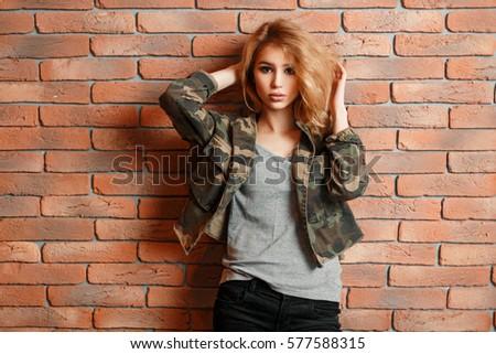 Shutterstock Pretty woman in military jacket posing near brick wall