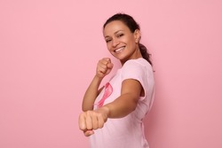 Pretty woman in pink t-shirt and cancer awareness ribbon stands in a fighting stance to mark the fight against cancer, in honor of October 1, smiles looking at camera, colored background, copy space