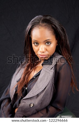 Pretty woman in pretty, see through black  blouse and a vest, looking at the camera with a friendly, flirting, expression