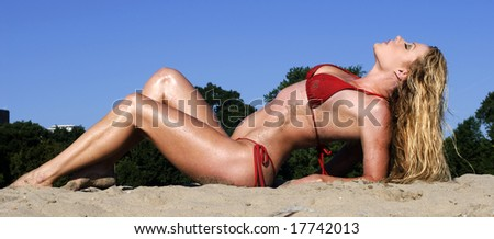 Pretty woman in red bikini arching her back on a beach on a sunny day