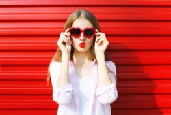 Pretty woman in red sunglasses blowing lips kiss over colorful background