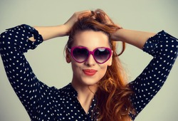 Pretty woman in red sunglasses smiling over green grey background