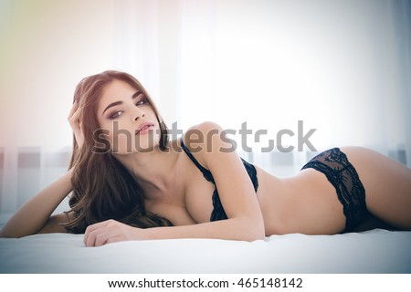 Pretty woman in sexy lingerie lying on the bed and looking at camera #465148142