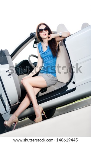 Pretty woman in sunglasses sits in the car with side door opened
