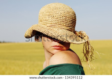 Pretty woman  in the hat in golden wheat