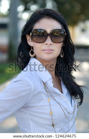 Pretty woman in the park with sun glasses on.