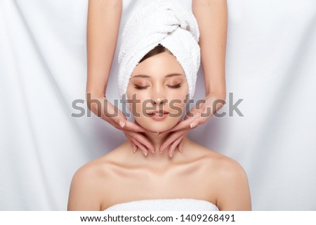 pretty woman in towel gets massage for her neck and face, fresh face receiving spa treatment, massaging and relaxation