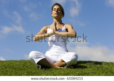 Pretty woman in white doing yoga outdoor