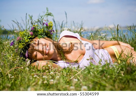 Pretty woman in  wreath of flowers sleep in  meadow on sunny day