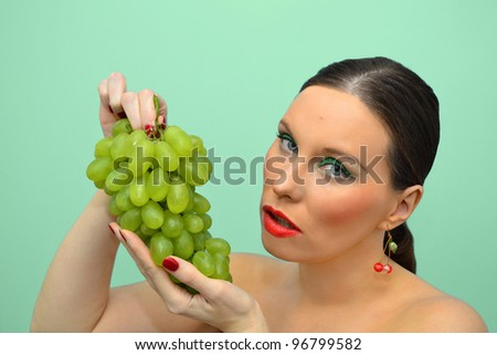 Pretty woman intending to eat bunch of grapes