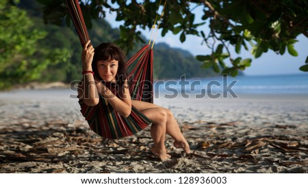 Pretty woman is laying on the hammock on the tropical ocean background.